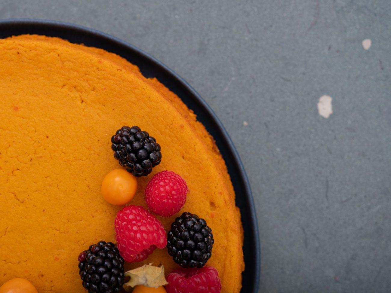 Rezept für Kürbiskuchen mit Keksboden und Beerentopping, Physalis, Teller