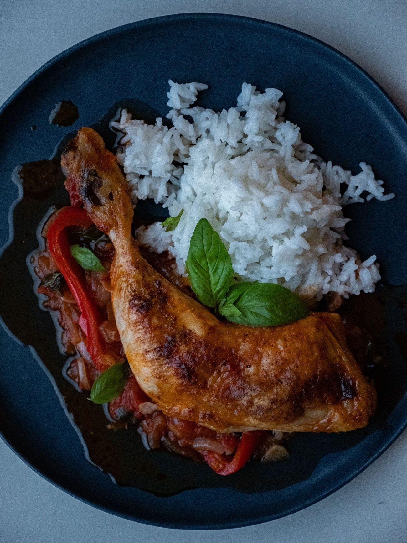 Rezept Hühnchenschenkel in Tomaten Paprika Soße, Reis, Teller, Basilikum