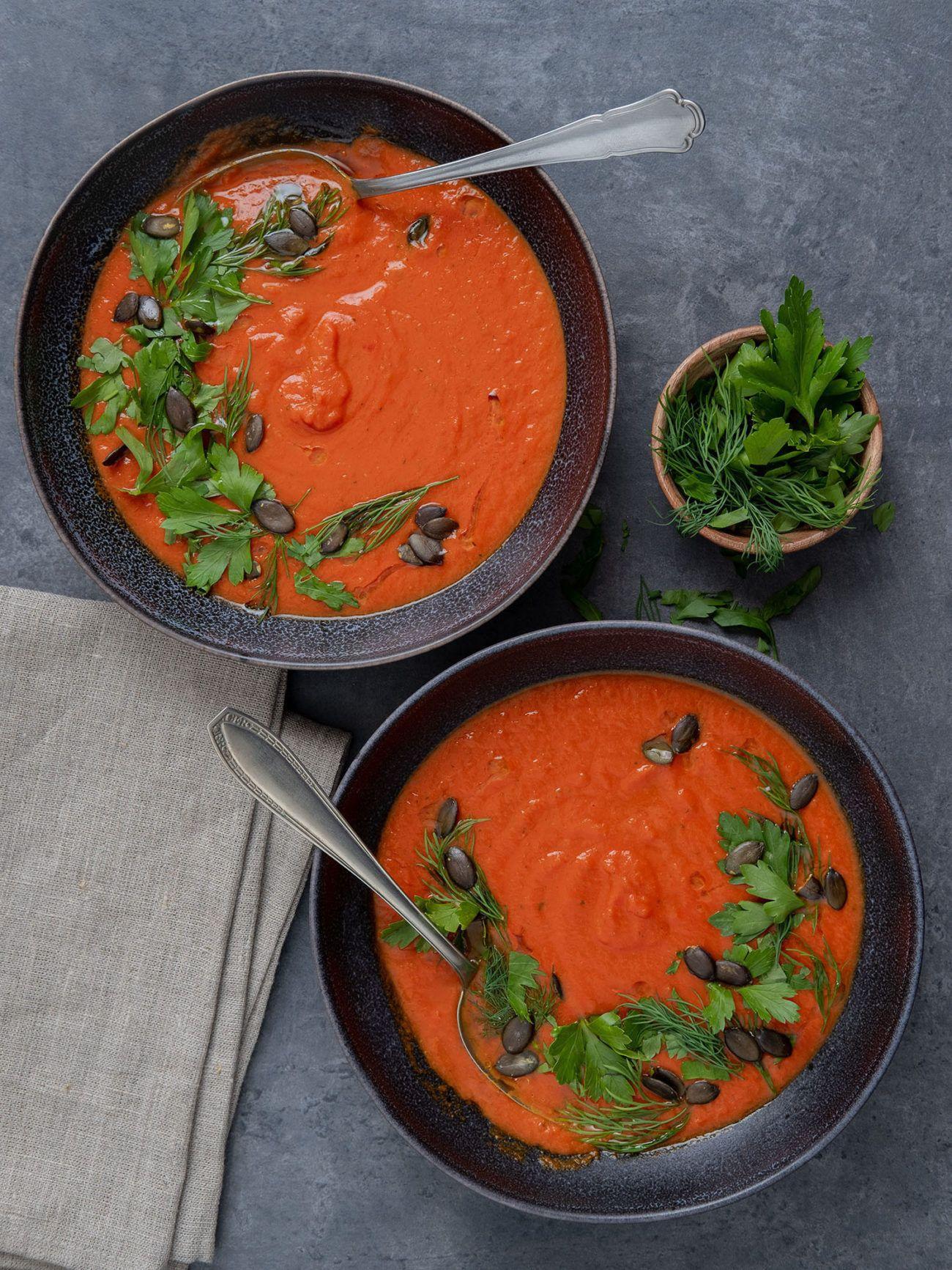 Rezept Tomaten-Kurkuma-Suppe mit Kürbiskern-Kräuter-Topping, Teller, Löffel, Kräuter
